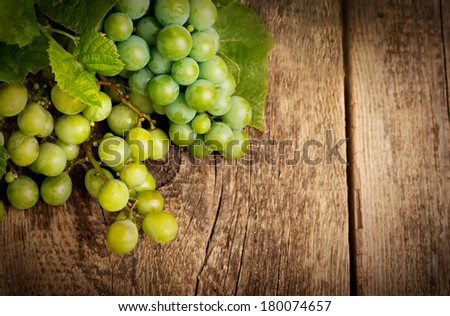Grapes with leaves on the wood background close up