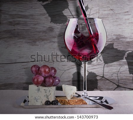 grapes with wine glass and cheese  against grunge wooden background