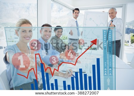 Graph against business team smiling at camera showing thumbs up