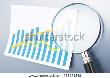 Graph and magnifying glass on gray background. Reading data. Looking graph with magnifying glass. Calculating, graphing and analyzing data.  - stock photo