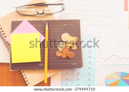 graph and money on the wooden table with vintage color concept - stock photo