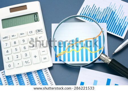 Graph, chart, magnifying glass and calculator.  Looking graph with magnifying glass. Calculating and analyzing data.