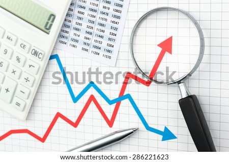 Graph, chart, magnifying glass, calculator and pen. Looking growth field of line graph with magnifying glass. Line graph and magnifying glass. Analyzing data.