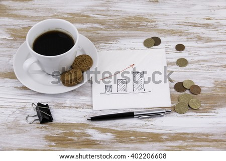 Graph on a napkin with a cup of coffee - stock photo
