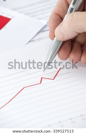 Graph on Documents and Human Hand Holding a Pen