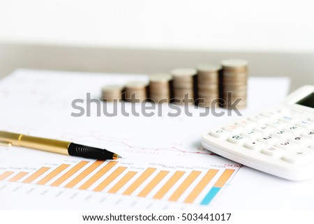 graph with calculator, pen and coins