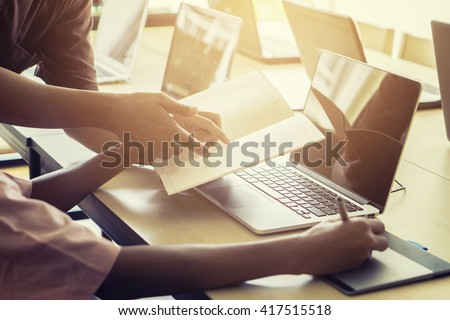 graphic design adviser consulting with young designer at classroom.teacher and young student discuss about new project of graphic design ,Selective focus,Vintage tone - stock photo