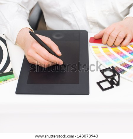 Graphic design, printing, advertising Graphic designer working with digitizer, magnifier, pantone palette, magazines on desk - stock photo