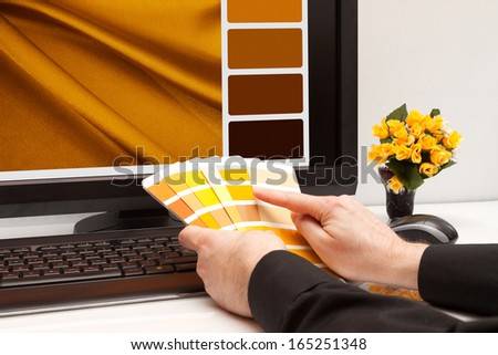 Graphic designer at work. Color samples. Brown, yellow images - stock photo