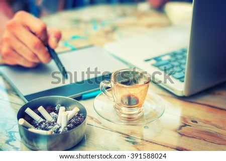 Graphic Designer drinking coffee during working with interactive pen display, digital Drawing tablet and Pen on a computer - stock photo