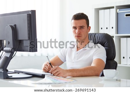 Graphic designer in polo shirt working on digital tablet