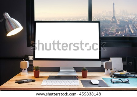 Graphic designer's workspace with cityscape view with a pen tablet, a computer and white background for text - stock photo