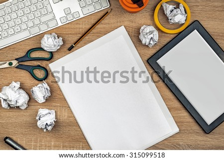 Graphic designer tabletop workspace with computer keyboard, digital tablet pc, blank drawing paper sheet, pencils, scissors, crumpled paper, top view overhead shot. - stock photo