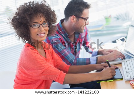 Graphic designer using a graphics tablet in her office with a colleague working behind - stock photo