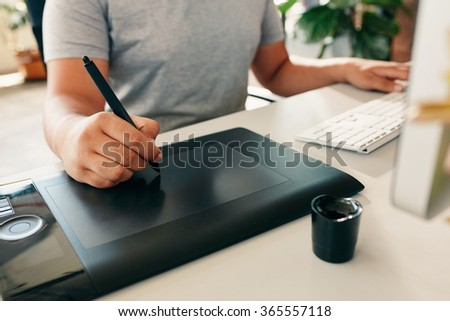 Graphic designer using digital tablet and desktop computer in the office. Close-up of designer's hand working with pen. - stock photo