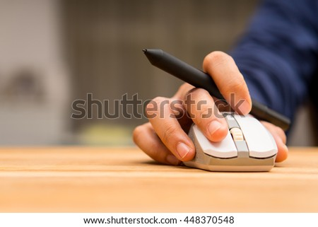 Graphic designer using pen mouse with laser mouse for working - stock photo