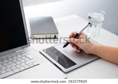 Graphic designer working on digital tablet and computer - stock photo