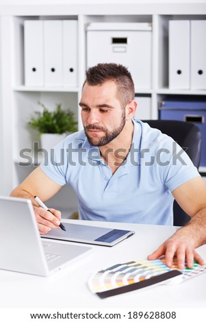 Graphic designer working on digital tablet and computer