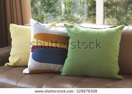 graphic pattern pillow and green pillows setting on leather sofa at comfortable living corner - stock photo