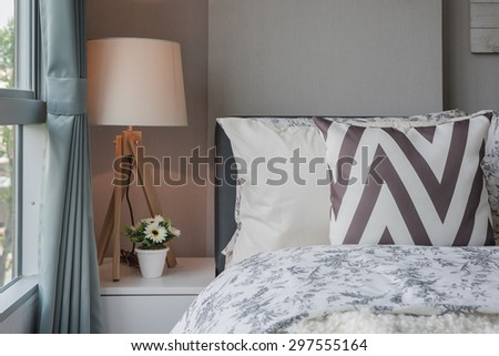 graphic pillow pattern in bedroom with modern lamp on table - stock photo