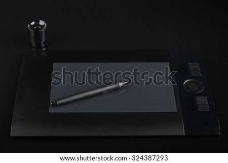 graphic tablet and pen and stand for nibs on black background