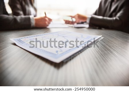 Graphical analysis graph which lies on the table in the background people - stock photo