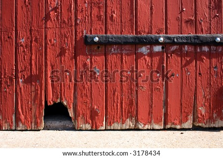 graphical photograph of a barn door with a mouse hole