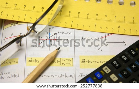 Graphs and charts of vectors (vector) theory together with glasses, calculator and wood pencil - stock photo