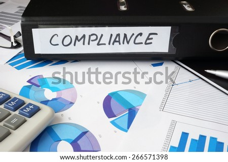 Graphs and file folder with label  Compliance . Business concept. - stock photo