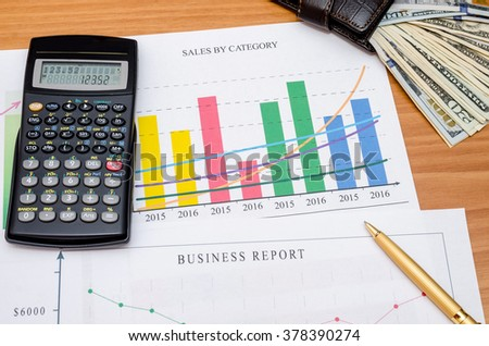 Graphs, charts, business table with money, calculator and pen on table