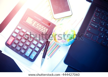 Graphs, charts, pen, calculator and mobile phone, business table. The workplace of business people. Vintage color filtered. - stock photo