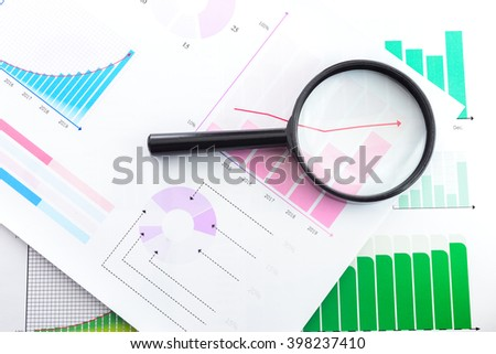 Graphs with magnifying - stock photo