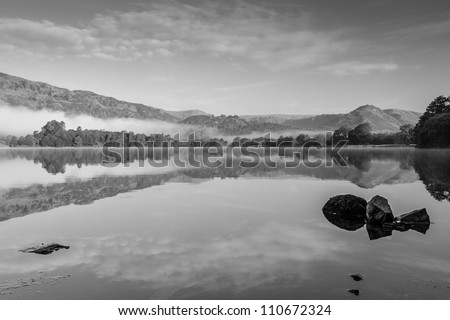 Grasmere and Helm Crag (the Lion and the Lamb) at first light on a misty morning - stock photo