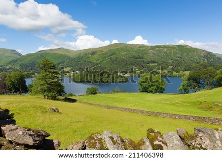 Grasmere Lake District Cumbria England UK with blue sky mountains and white clouds and stone wall on a beautiful summer day in this National Park
