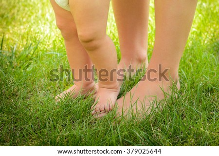Grass background with baby feet - stock photo