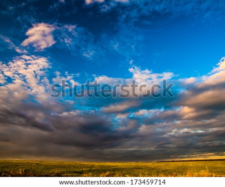 grass field dramatic sky and clouds at sunset (sunrise) - stock photo
