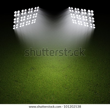 Grass field lit with bright spotlights - stock photo
