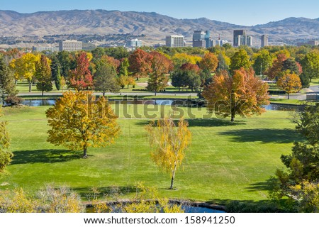 Grass field of a park and mountains with the City of Boise Idaho  - stock photo