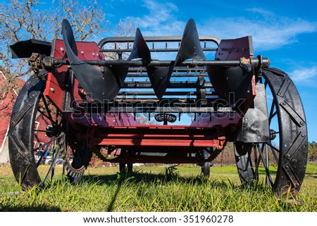 Grass field with an old farm tractor - stock photo