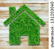 Grass home icon on wooden - stock photo