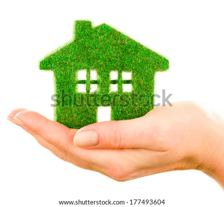 Grass home isolated on white background in human hands - stock photo