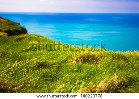 Grass ledge and ocean along coast in Ireland - stock photo
