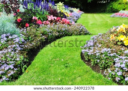 Grass Pathway and Flowerbed in a Beautiful Landscaped Garden - stock photo