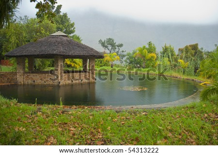 Grass roofed, brick gazebo, surrounded by a pond and grass, with storm clouds in the background - stock photo