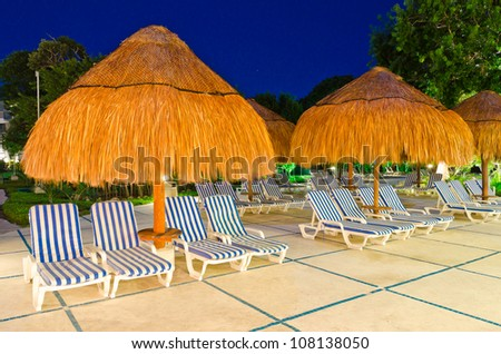 Grass umbrella with lounges at a caribbean resort at night, dawn time