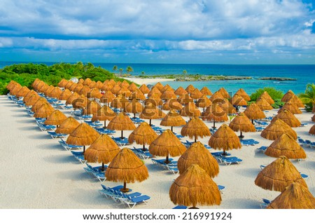 Grass umbrellas and the lounges on the beach of the caribbean, mexican luxury resort. - stock photo