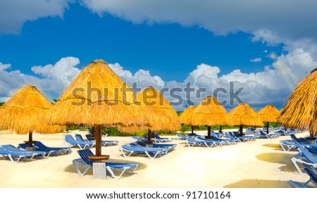Grass umbrellas on  the beach of the caribbean resort