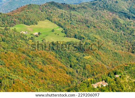 grassland, colorful forest and small villages on hills in fall, Ariege, France