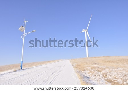 grassland road with wind turbine,Solar and wind power lamp - stock photo