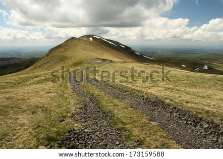 grassland with gravel road at Monts du Cantal - stock photo